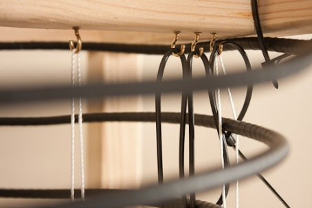 Hooks screwed into the wooden support system help hold ropes and zip ties to support the antenna